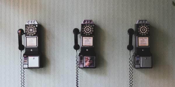 three rotary pay phones on a wall